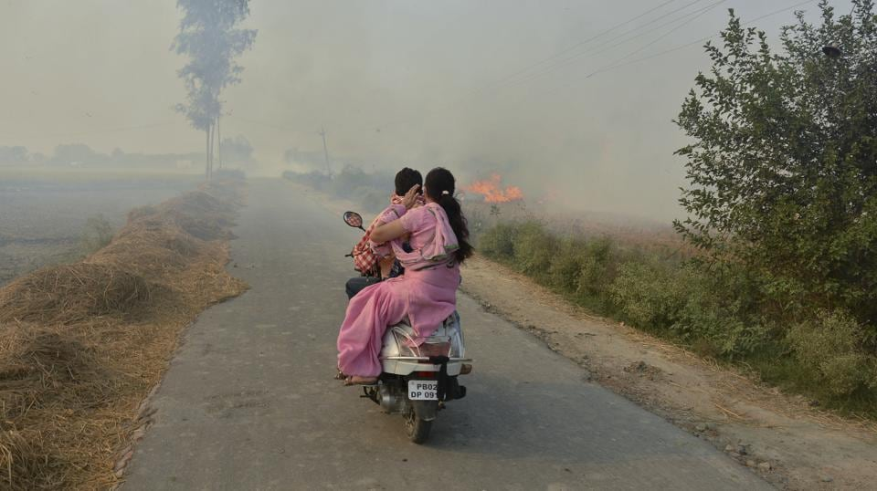 A couple on a scooter ride through smoke caused by farmers burning crop stubble on the outskirts of Amritsar, Punjab. (Prabhjot Gill / AP)