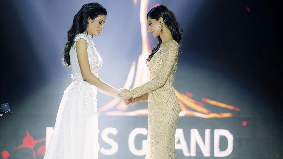 Finalist Clara Sosa of Paraguay (L), hold hands with Meenakshi Chaudhary of India before the winner was announced during Miss Grand International 2018 in Yangon, Myanmar. Miss Grand International 2018 Sosa fell while the first runner-up Miss India Chaudhary tried to help. Sosa soon recovered and had a teary smile as she was crowned. (Miss Grand International Co., Ltd. via AP)