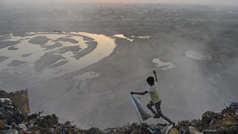 A child runs across a mountain of garbage at Bhalswa landfill in New Delhi. (Sanchit Khanna / HT Photo)