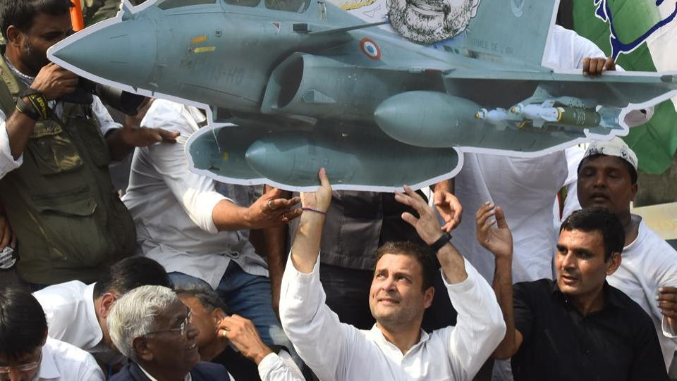 Congress president Rahul Gandhi on top of a vehicle holds a cutout of Rafael aircraft during a protest march at the CBI Headquarters demanding the reinstatement of CBI Director Alok Verma in New Delhi. (Vipin Kumar / HT Photo)