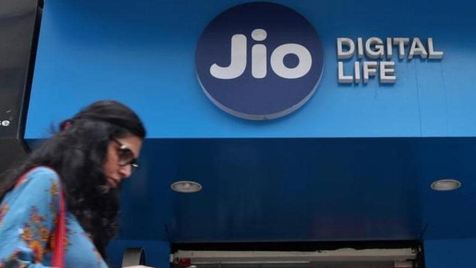 A woman checks her mobile phone as she walks past a mobile store of Reliance Industries' Jio telecoms unit, in Mumbai.