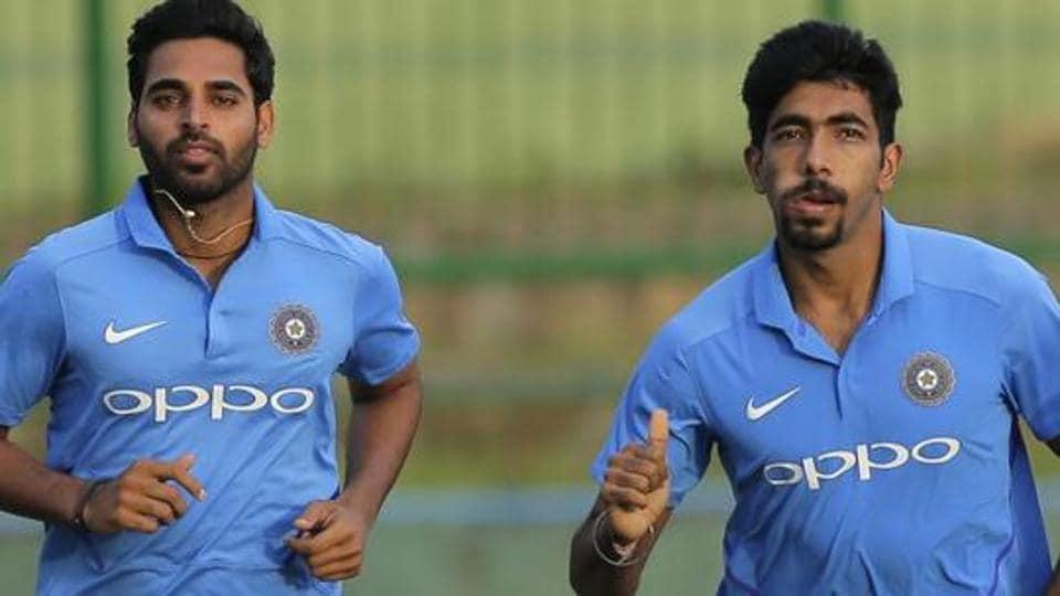 Indian cricketers Bhuvneshwar Kumar and Jasprit Bumrah jog during a practice session.