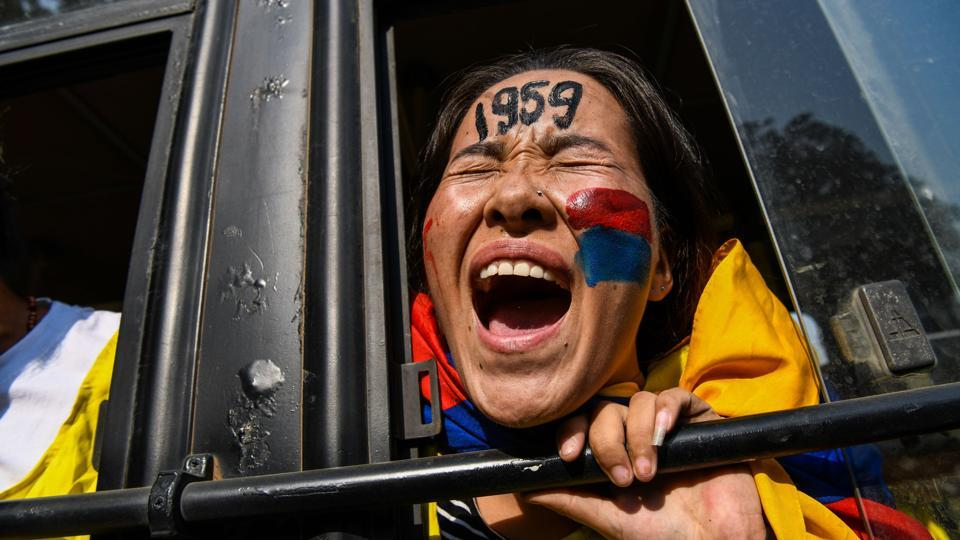 An exiled Tibetan youth shout slogans from a police bus as she protests against a visit of Chinese ministers including the minister of public security Zhao Kezhi and other high-level ministers to India in New Delhi. (Chandan Khanna / AFP)