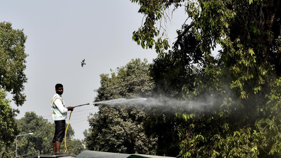 NDMC worker spray water to clean dust gathered on trees at Mansingh Road as pollution mounts in the national capital on October 17, 2018. The Supreme Court on Tuesday also set a two-hour window for the use of low-emission firecrackers on Diwali night but didn't impose any ban on the sale of firecrackers in the National Capital Region. (Vipin Kumar / HT Photo)