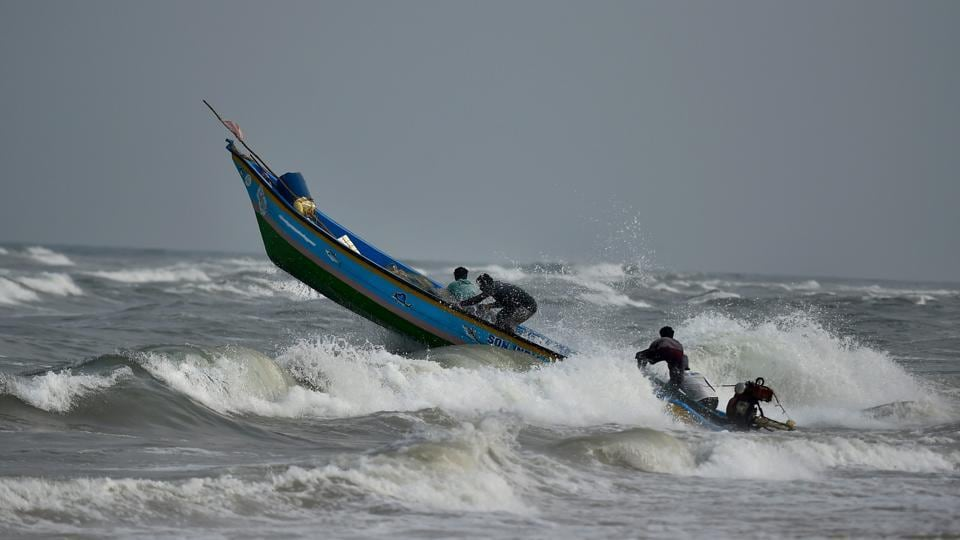 Fishermen steer their boat while out to catch fish near Marina Beach, in Chennai. The North East Monsoon is expected to set in later this month. (PTI)