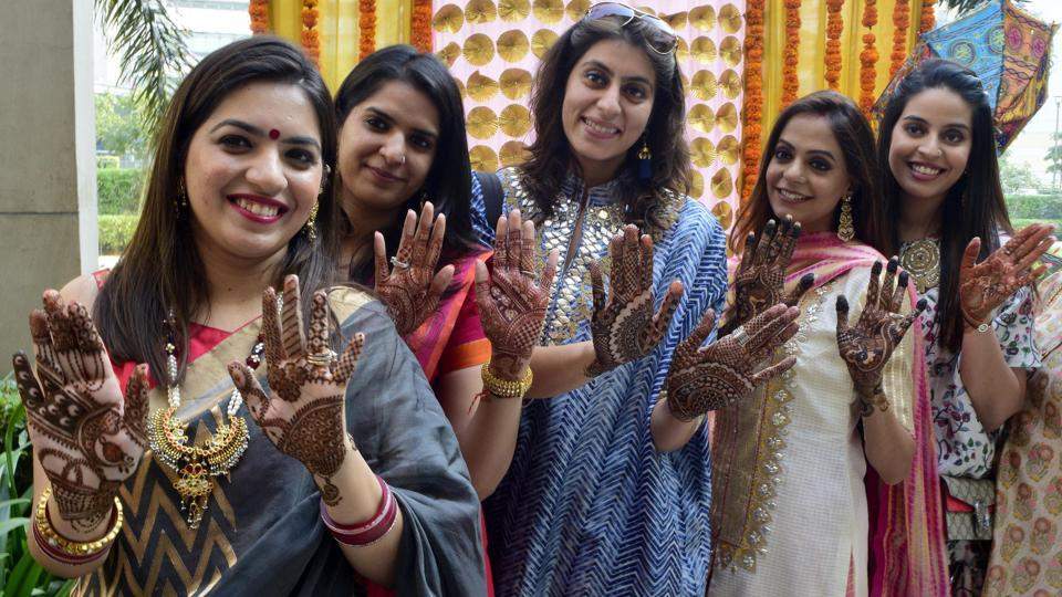 Women show their mehendi (henna) applied hands on the eve of Karva Chauth festival in Amritsar on Friday. Karwa Chauth is a tradition according to which married women or those who are of marriageable age pray for the safety and long life of their husbands, fiances or preferred husbands. (Sameer Sehgal/ht)