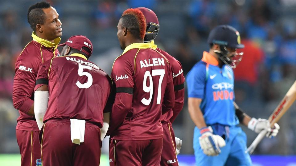 West Indies bowler Marlon Samuels (L) celebrates with team mates after taking the wicket of India captain Virat Kohli (R). (AFP)