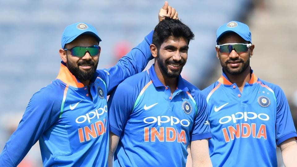 Jasprit Bumrah (C) celebrates with captain Virat Kohli (L) and Shikhar Dhawan after taking the wicket of Kieran Powell.