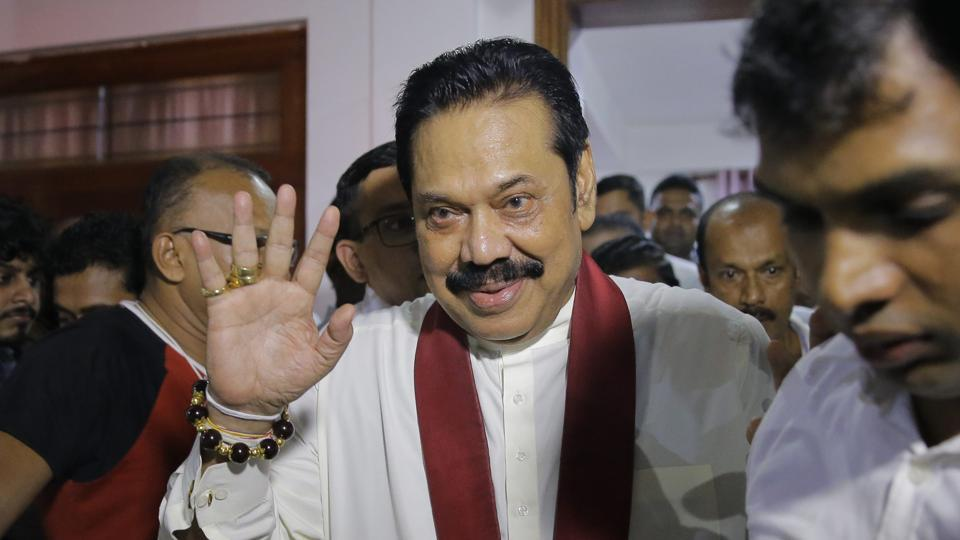 Newly appointed Sri Lankan Prime Minister Mahinda Rajapaksa, centre, leaves a Buddhist temple after meeting his supporters in Colombo, Sri Lanka, October 26, 2018