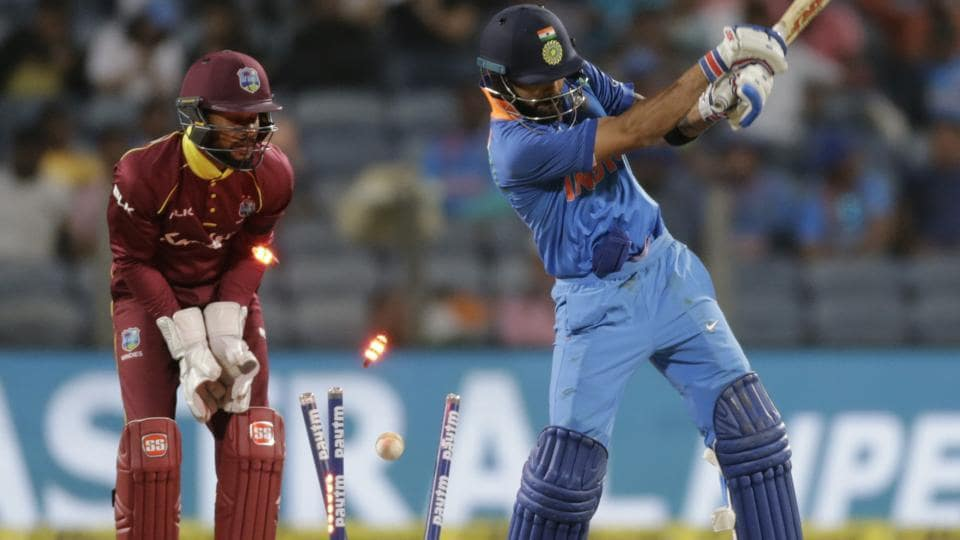 India's captain Virat Kohli, right, is bowled out by West Indies' bowler Marlon Samuels.