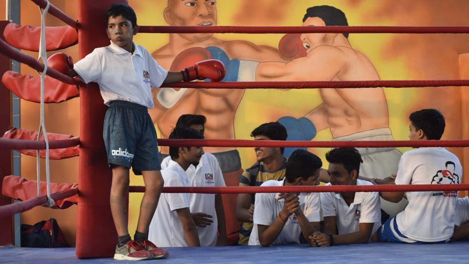 A boy rests ringside at BM Boxing Academy in Najafgarh. This academy, whose founder is Brij Mohan, was inaugurated recently. Until a few years ago, boxing didn't hold much sway in Najafgarh, but this area where youngsters have traditionally chosen kabaddi, wrestling or cricket, is becoming Delhi's nursery for boxing. (Vipin Kumar / HT Photo)
