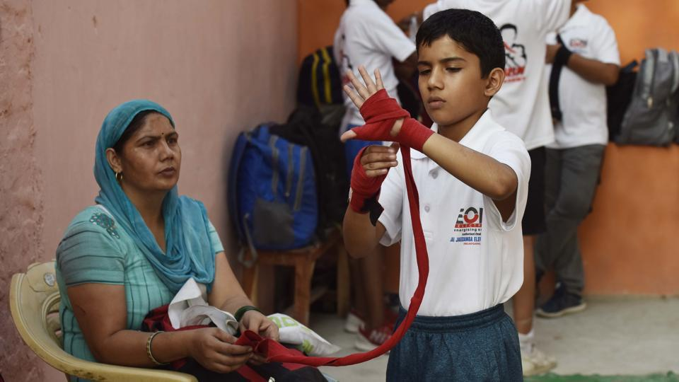 A young boxer puts on hand wraps before a training session. Rohit Shokeen, a boxing coach at Najafgarh stadium, said that children there are more focused on sports than studies and parents support them. Most youngsters want to get into the armed forces, and sports only enhance their chances. (Vipin Kumar / HT Photo)