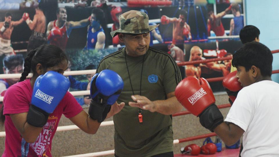 Boxing coach Anil Fauji trains students. Najafgarh Boxing Academy, which started three years ago, has 125 students and claims 40 national level players as products. The academy's brick-red walls have black and white posters of American boxers, such as Floyd Mayweather, Mike Tyson, Muhammad Ali and Indian boxing champions such Mary Kom, Akhil Kumar, Vijender Singh and Vikas Krishnan, among others. (Vipin Kumar / HT Photo)