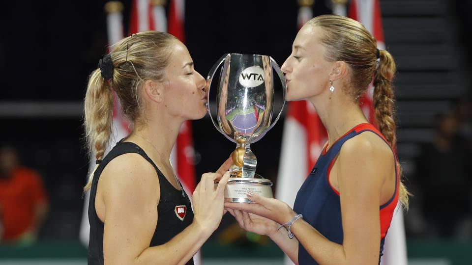 France's Kristina Mladenovic, right, and Hungary's Timea Babos celebrate with the trophy after winning the doubles final against Czech Republic's Katerina Siniakova and Czech Republic's Barbora Krejcikova at the WTA tennis finals in Singapore.