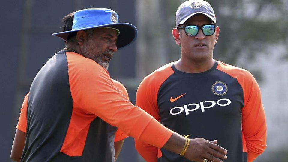 India's Mahendra Singh Dhoni, right, listens to bowling coach Bharat Arun during a practice session.