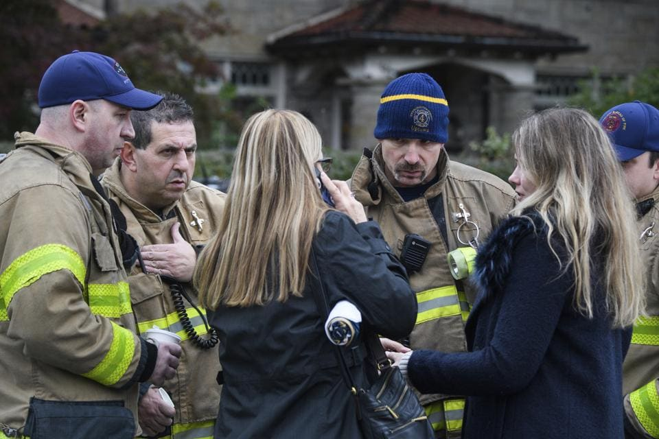 Firefighters talk to people arriving at a scene of a deadly shooting at the Tree of Life synagogue, Saturday, Oct. 27, 2018, in the Squirrel Hill section of Pittsburgh.
