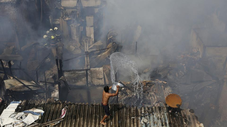 A boy pours water trying to douse a fire at a slum in Mumbai. Two children were injured and nearly 70 houses were gutted in a fire that broke out at around 11.30 am and was brought under control by 1 pm. A senior fire department official said that 7-8 gas cylinder blasts led to the massive blaze. (Rafiq Maqbool / AP)