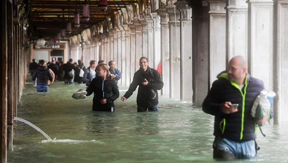 Tourists under arches next to the flooded St Mark's Square during a high-water (Acqua Alta) alert in Venice on October 29.