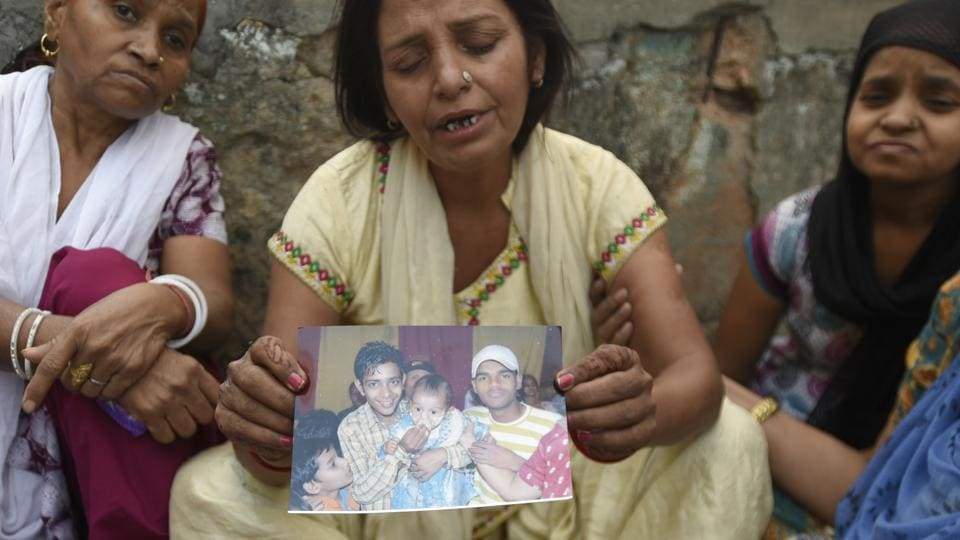 Family members of Sushil who, along with two other men, was killed after being run over by a train in outer Delhi's Nangloi, on October 29, 2018. Police said the three men were drinking alcohol on the railway tracks and could not sense the train's speed.