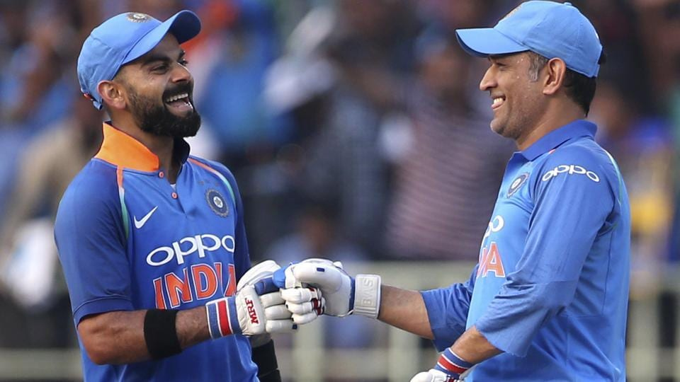 Virat Kohli, left, shares a light moment with teammate Mahendra Singh Dhoni after scoring 10,000 runs in one-day internationals.