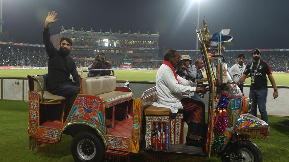 FILE: Pakistani former captain Misbah ul Haq (L) rides on an auto-rickshaw as he waves to crowd during the third and final Twenty20 International match between the World XI and Pakistan at the Gaddafi Cricket Stadium in Lahore.