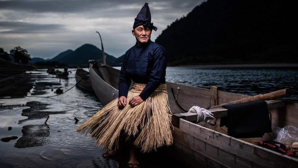 Cormorant master Shuji Sugiyama poses for a portrait in Gifu, Japan. As the night turns pitch black, fires burn alongside a river in Japan's Gifu with a handful of men preparing for a ritual that dates back over 1,300 years: fishing with cormorants. (Martin Bureau / AFP)