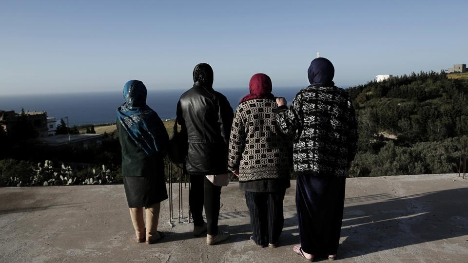 Women whose sons went missing look at the shoreline in the town of Ras Jabal, Bizerte, Tunisia. The boys grew up within sight of the sea that took them away, rambling along paths and climbing rocks that would later be the launching pad for their flimsy rafts. (Nariman El-Mofty / AP)