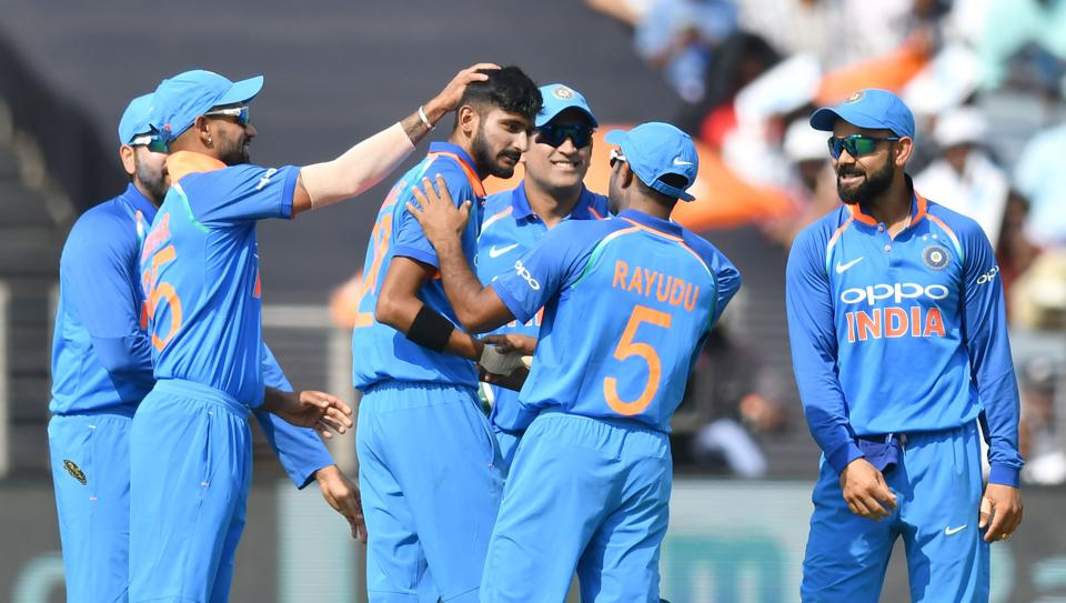 India bowler Khaleel Ahmed (C) celebrates with captain Virat Kohli (R), Mahendra Singh Dhoni and Shikhar Dhawan (L) after taking the wicket of West Indies cricketer Marlon Samuels