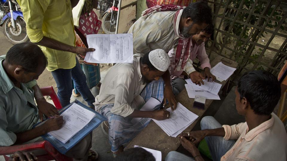 People whose names were left out in the National Register of Citizens (NRC) draft fill their forms to file appeals near a NRC center on the outskirts of Guwahati.