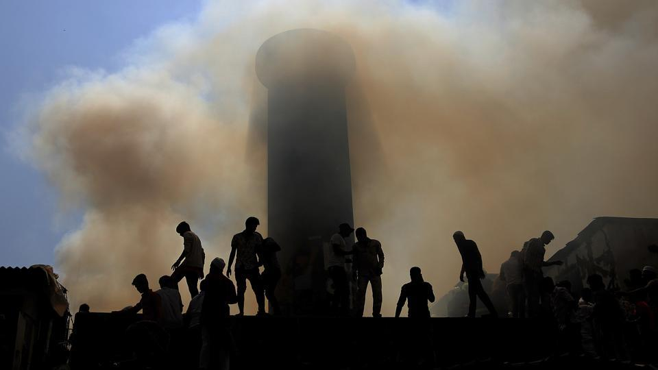 People are silhouetted against the smoke as firefighters try to douse a fire at a slum in Mumbai on October 30, 2018. (Rafiq Maqbool / AP)