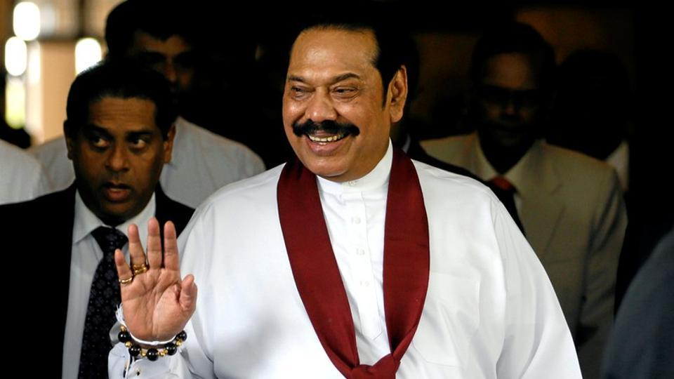 Sri Lanka's newly appointed Prime Minister Mahinda Rajapaksa waves at the staff after participating in the ceremony to assume his duties as the minister of finance and economic affairs at the finance ministry in Colombo, Sri Lanka October 31, 2018.