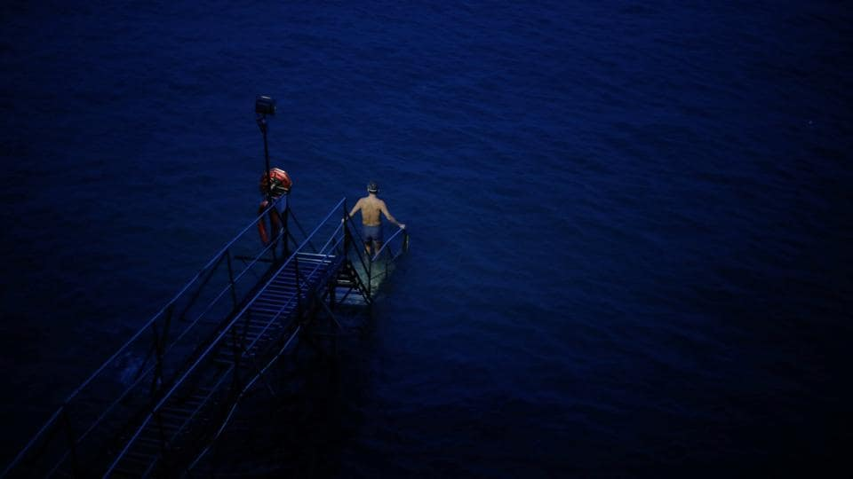 A swimmer enters the sea before dawn at the Sai Wan Swimming Shed in Hong Kong. For nearly 30 years, Sandy Lam has been rising early each day for a dip in the sometimes choppy waters off the western edge of Hong Kong island, next to one of the world's busiest ports. (REUTERS / Hannah McKay)