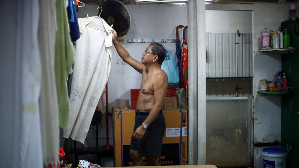 Lam, 68, hangs a towel to dry in the men's changing room at the Sai Wan Swimming Shed. He is part of a tightly-knit community of around 50 mostly elderly citizens who are regular visitors to Sai Wan Swimming Shed, tucked away off a steep hill, providing basic changing rooms and showers. (REUTERS / Hannah McKay)