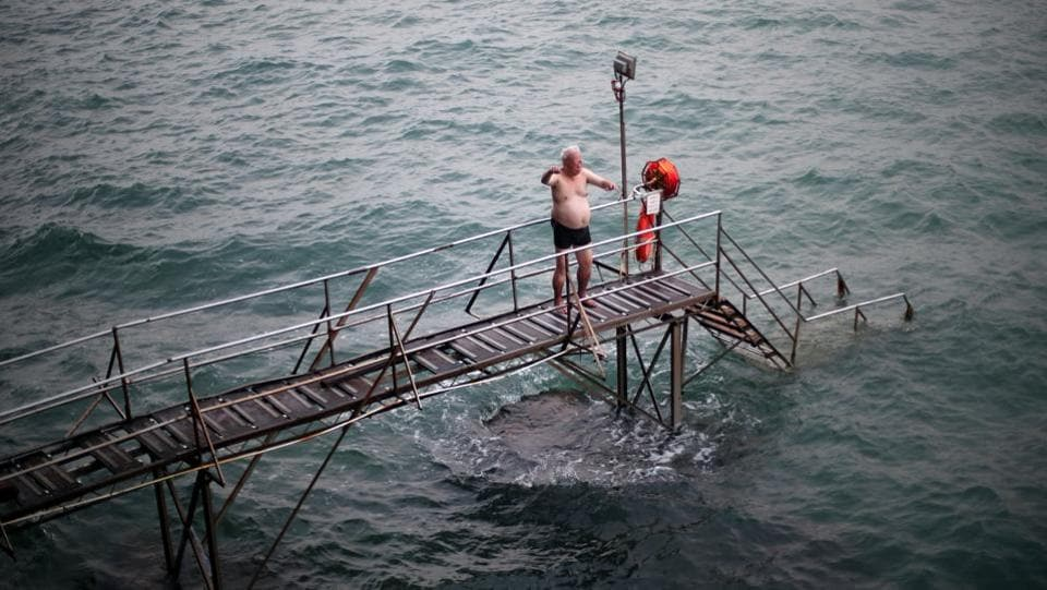 The residents, many of who have been swimming there for decades, plunge into the waters from steps reached by a spindly wooden bridge propped up on the rocks. (REUTERS / Hannah McKay)