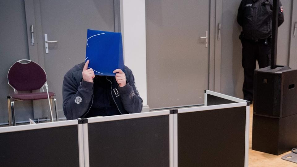 Former nurse Niels Hoegel, accused of killing more than 100 patients in his care, hides behind a folder as he arrives in the courtroom, in Oldenburg, northern Germany, for the start of his trial. (Julian Stratenschulte / Pool / AFP)