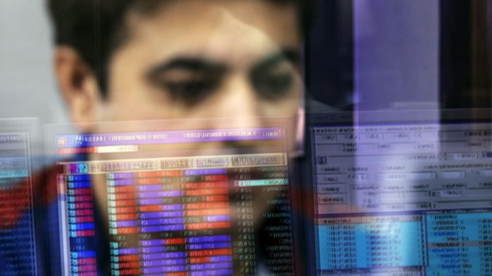 An employee is reflected in a glass panel as he monitors securities on a computer monitor at a brokerage firm in Mumbai.