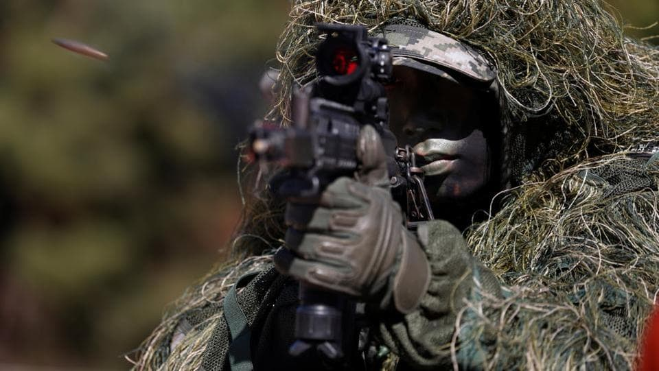 A South Korean marine in action during their regular drill on Yeonpyeong Island, South Korea. (Jeon Heon-Kyun / Pool via REUTERS)
