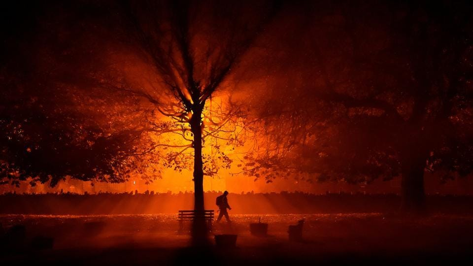 A man uses a torch to walk through a park during cold fog at night in Athboy, Ireland. (Clodagh Kilcoyne / REUTERS)