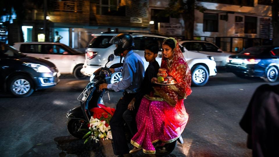 A Hindu family leaves on a scooter before performing rituals during the Karwa Chauth festival at a temple in New Delhi on October 27, 2018. (Chandan Khanna / AFP)
