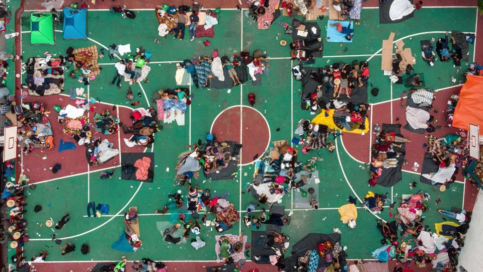 Aerial view of Honduran migrants heading in a caravan to the US, resting in a basketball pitch in San Pedro Tapanatepec, Oaxaca state, southern Mexico. (Guillermo Arias / AFP)