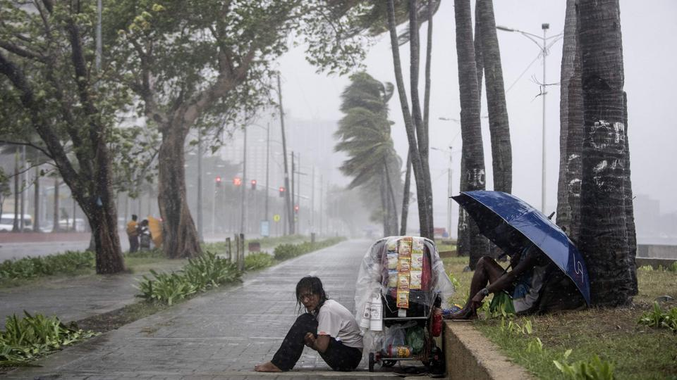 A streetside vendor shivers in the rain as weather patterns from Typhoon Yutu affect Manila Bay, in the Philippines. (Noel Celis / AFP)