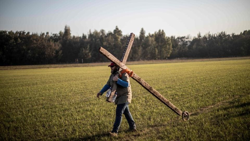 "Bert Human - known as the 'Silent Preacher' - a follower of South African Christian revival evangelist Angus Buchan carries a cross while arriving at an informal airfield outside Pretoria, for the ""It's Time"" prayer, an event poised to become the Southern Africa's biggest ever prayer meeting. (Marco Longari / AFP)"