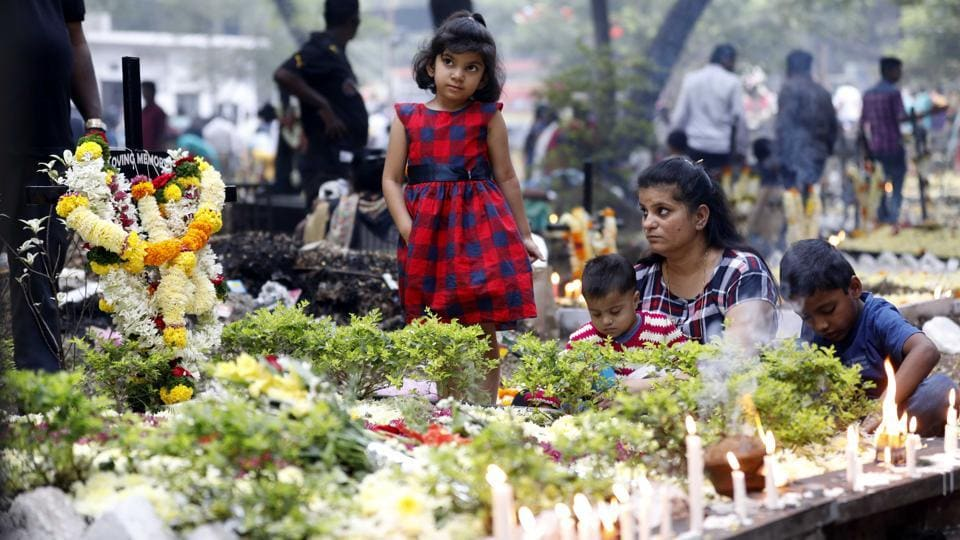 A family sits around the grave of their loved one after decorating it with candles and flowers. Christians follow the annual observance by offering flowers and lighting candles on the graves of their departed loved ones on All Souls Day at the St Sepulclchers cemetery in Pune,on Friday. (Rahul Raut/HT PHOTO)