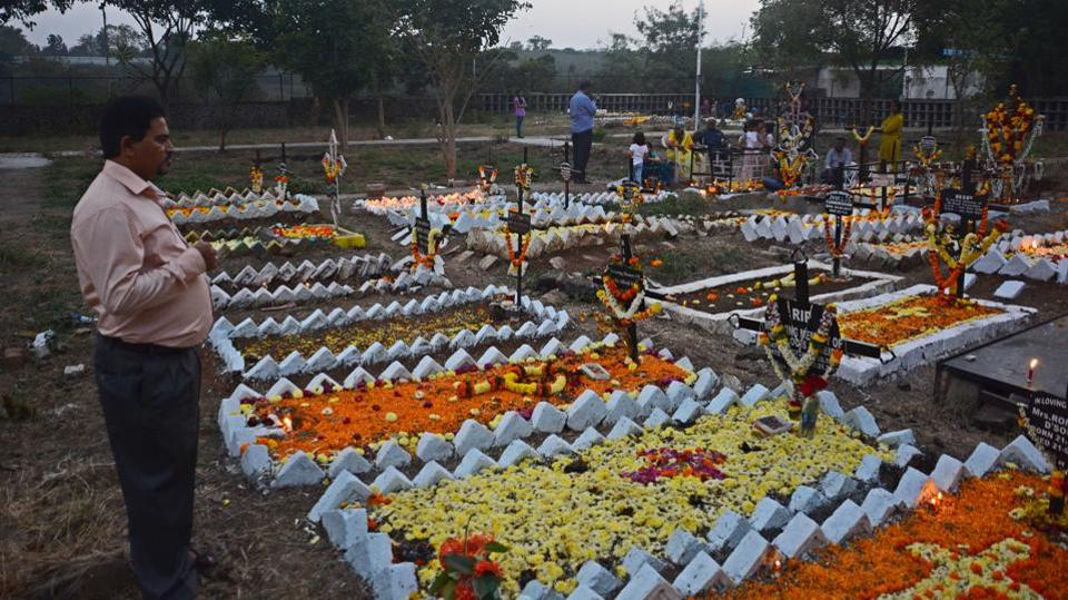 A man prays in front of his relative's grave. Catholic devotees pay their respects and decorate the graves of a deceased family members at a cemetery in Wadagaon Sheri during All Souls Day in Pune,on Friday. (Shankar Narayan/HT PHOTO)
