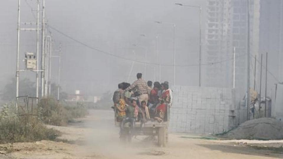 Labourers arrive for work at a building construction site on a hazy morning in Greater Noida, near New Delhi,  on October 26.
