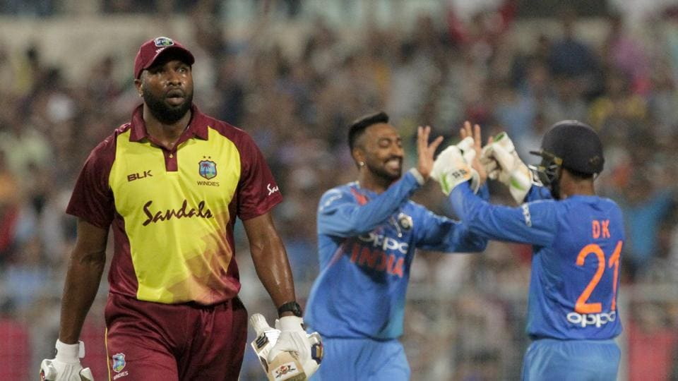 West Indies' Kieron Pollard, left, leaves the filed after being dismissed as India's Krunal Pandya, center, celebrates with teammate Dinesh Karthik during the first Twenty20 international cricket match between India and West Indies in Kolkata (AP)