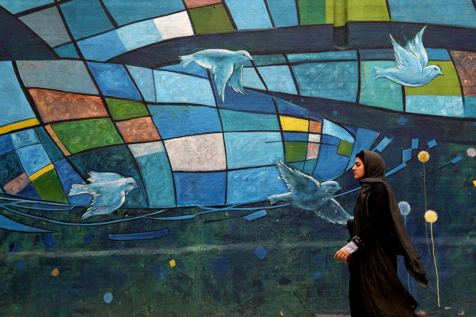 An Iranian woman walks past colourful walls in the capital Tehran. Iran's President Hassan Rouhani said the Islamic republic 'will proudly bypass sanctions' by the United States that took effect on Monday targeting the country's oil and financial sectors.