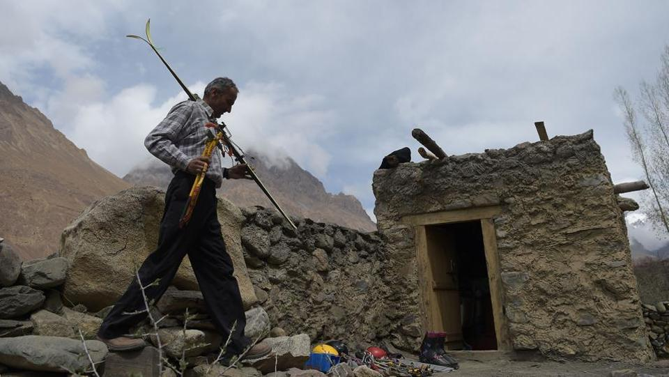 """Rehmatullah Baig, who climbed and measured K-2 in 2014 for the first time after the mountain's initial discovery, arranges mountaineering gear at his home in Shimshal village, Hunza valley, Pakistan. At 8,611 metres, K2 is not quite as high as Mount Everest's 8,848 metres, but its technical challenges have earned it the nickname """"the Savage Mountain"""" and dozens have lost their lives on its treacherous flanks. (Aamir Qureshi / AFP)"""