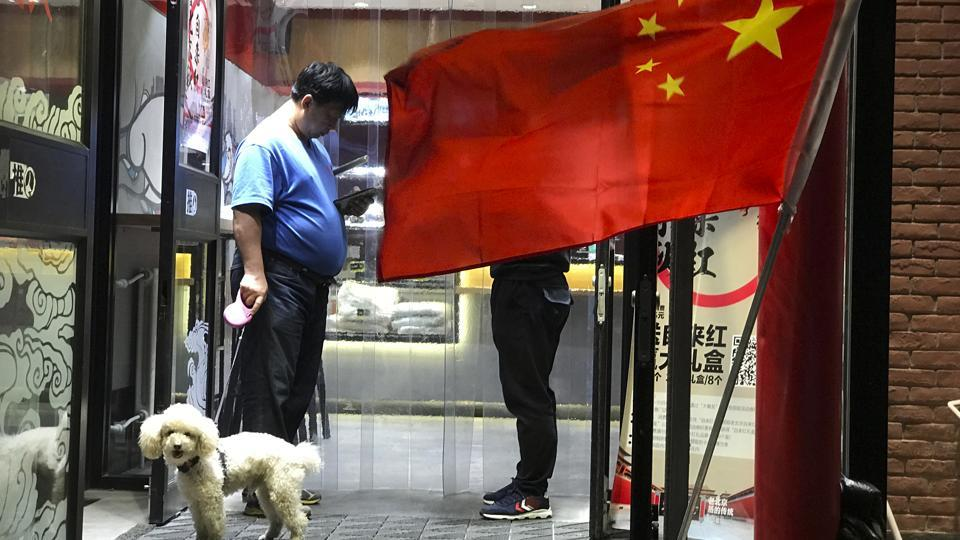 A man walks his dog as he leaves a restaurant flying the Chinese national flag in Beijing, China.