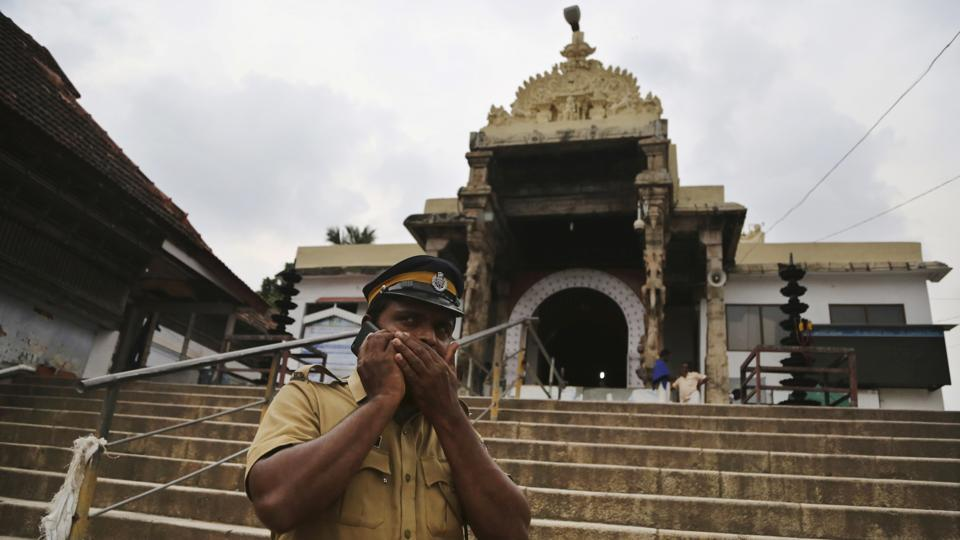 An Indian police officer talks on a phone while standing guard outside the 16th-century Sree Padmanabhaswamy temple in Thiruvananthapuram, Kerala. Synagogues, mosques, churches and other houses of worship are routinely at risk of attack in many parts of the world. And so worshippers themselves often feel the need for visible, tangible protection even as they seek the divine. (Aijaz Rahi / AP)